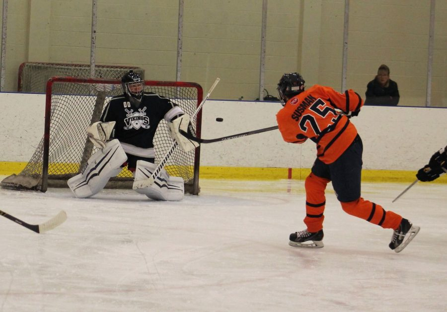 Senior Adam Susman launches a slap shot from just outside the faceoff circle