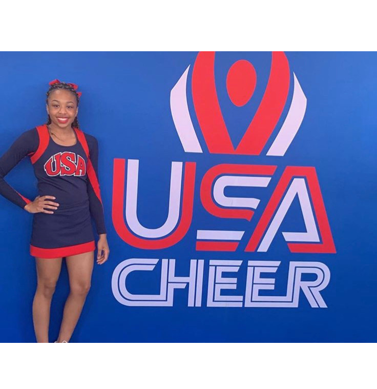 Iry Conley in front of USA Cheer sign