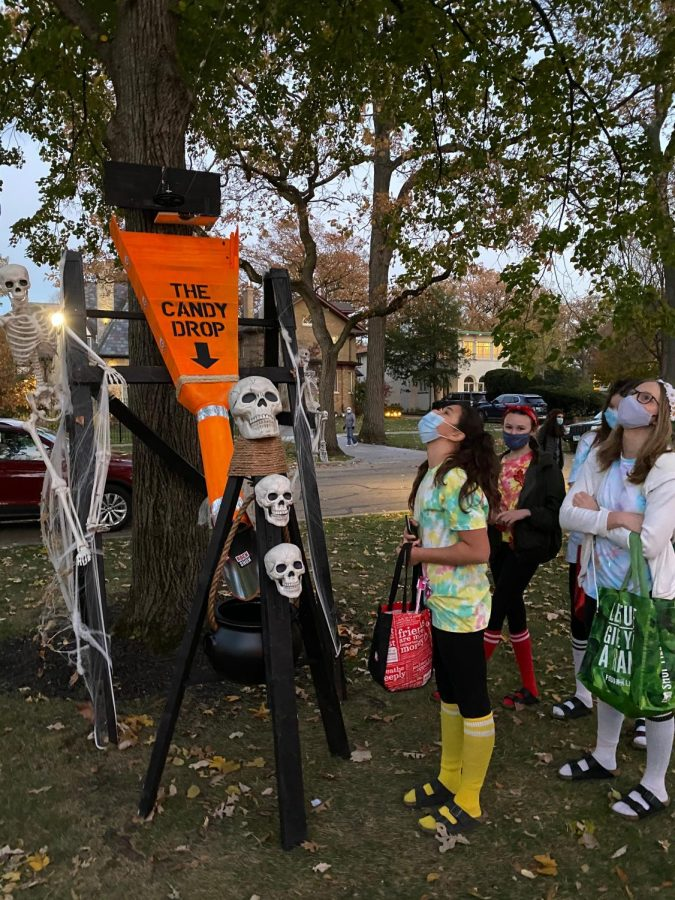 Trick-or-treaters look on as Halloween candy makes its way to the ground